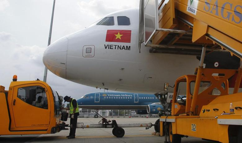 A worker pumps fuel into a Vietjet Air A320 aircraft, in front of a Vietnam Airlines aircraft at Tan Son Nhat airport in Vietnam's southern Ho Chi Minh city October 20, 2013. REUTERS/Kham