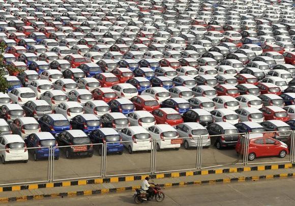 A man rides his motorbike past parked Hyundai cars ready for shipment at a port in Chennai October 1, 2013. REUTERS/Babu/Files