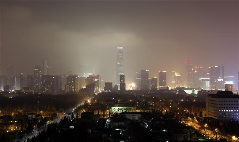 Buildings are pictured amid the heavy haze at night in Beijing's central business district, January 30, 2014. REUTERS/Jason Lee
