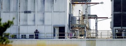 Um guarda usa um binóculos para monitorar as instalações da General Motors em São José dos Campos. O emprego na indústria brasileira voltou a enfraquecer em dezembro ao recuar 0,3 por cento e encerrou 2013 com queda acumulada de 1,1 por cento, segunda taxa negativa seguida. 24/07/2012 REUTERS/Roosevelt Cassio