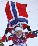 Норвежская лыжница Майкен Касперсен Фалла радуется победе в спринте на Играх в Сочи 11 февраля 2014 года. Норвежская лыжница Майкен Касперсен Фалла и ее соотечественник Ола Виген Хаттестад выиграли золотые медали в спринте свободным стилем. REUTERS/Kai Pfaffenbach