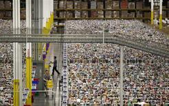 Unos trabajadores en la bodega del centro de distribución de Amazon en Phoenix, EEUU, nov 22 2013. Los inventarios mayoristas en Estados Unidos subieron menos de lo esperado en diciembre, lo que sugiere una moderación en el ritmo de acumulación de existencias hacia fin de año que podría dar pie a una reducción de las estimaciones de crecimiento del cuarto trimestre. REUTERS/Ralph D. Freso