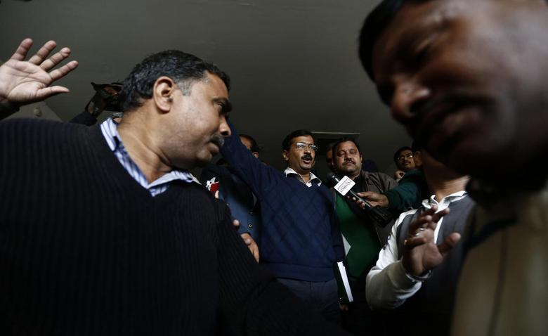 Delhi's Chief Minister Arvind Kejriwal (C), chief of the Aam Aadmi (Common Man) Party (AAP), leaves after addressing the media during a news conference in New Delhi February 11, 2014. REUTERS/Adnan Abidi