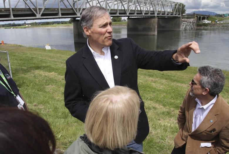 Washington State Governor Jay Inslee looks over the scene as a span of highway bridge sits in the Skagit River May 24, 2013 after collapsing near the town of Mt Vernon, Washington late Thursday. REUTERS/Cliff DesPeaux)