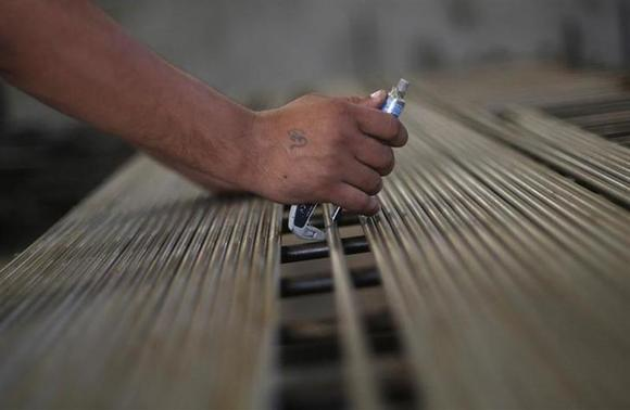 An employee checks the gauge of steel rods at the production line inside Hallmark steel factory in Bhiwadi in Rajasthan September 30, 2013. REUTERS/Adnan Abidi/Files