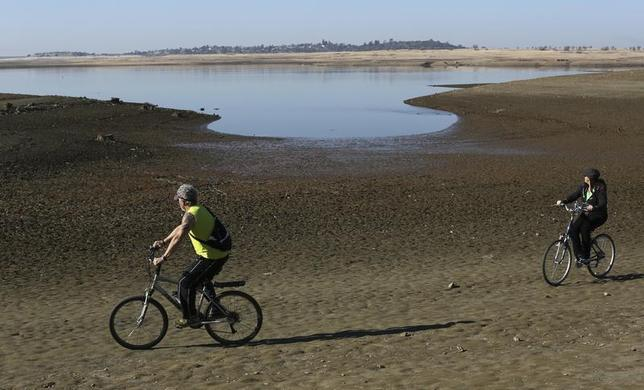 Visitors ride bicycles near the receding waters at Folsom Lake, which is 17 percent of its capacity, in Folsom, California January 22, 2014. REUTERS/Robert Galbraith
