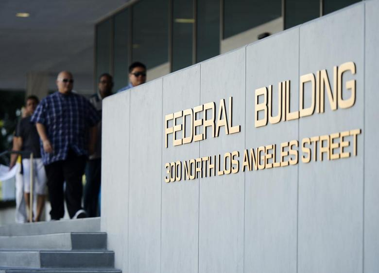 People walk out of the Federal Building, where the Internal Revenue Service (IRS) offices are located, in Los Angeles, California October 1, 2013. REUTERS/Kevork Djamsezian