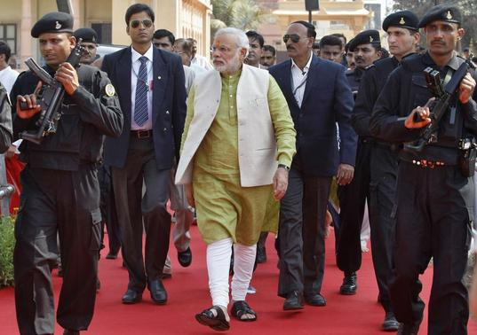 Narendra Modi (C), prime ministerial candidate for the Bharatiya Janata Party (BJP) and Gujarat's chief minister, is surrounded by his security personnel as he arrives to attend a public meeting at Somnath in Gujarat February 1, 2014. REUTERS/Amit Dave