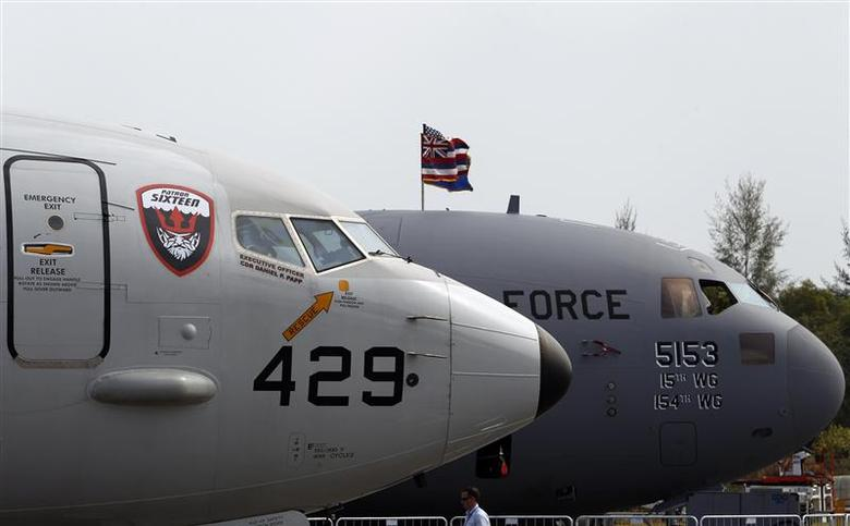 A U.S. Navy Boeing Poseidon P8 sits on display next to a U.S. Air Force C-17A Globemaster III aircraft (R) at the Singapore Airshow February 11, 2014. REUTERS/Edgar Su