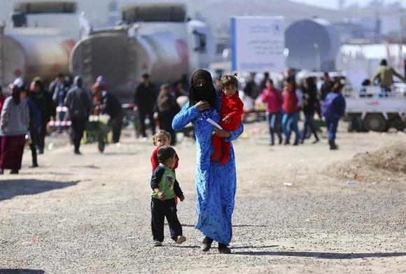 A Syrian refugee woman walks to receive her share of humanitarian aid in Quru Gusik refugee camp on the outskirts of Arbil, in Iraq's Kurdistan region, February 10, 2014. REUTERS/Stringer