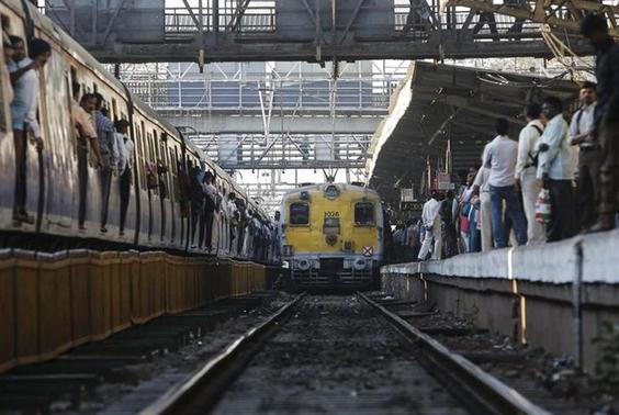 Commuters wait on a crowded railway platform as a train enters a suburban station in Mumbai February 12, 2014. REUTERS/Danish Siddiqui
