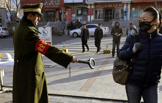 A pedestrian reacts as a security officer holds out a detector on a street in Urumqi, Xinjiang Uighur autonomous region, November 17, 2013. REUTERS/Rooney Chen
