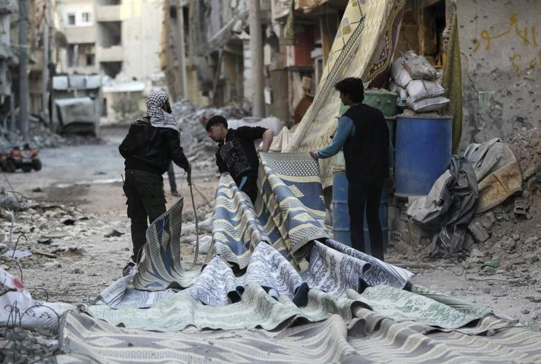 Free Syrian Army fighters pull carpets along a rubble-filled street as they prepare to use them as curtains to provide cover from snipers loyal to Syria's President Bashar al-Assad in Deir al-Zor, eastern Syria February 11, 2014. REUTERS/Khalil Ashawi