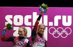 Winner Germany's Natalie Geisenberger (R) and second-placed compatriot Tatjana Huefner celebrate with their bouquets at the flower ceremony for the women's luge singles competition during the 2014 Sochi Winter Olympics, February 11, 2014. REUTERS/Fabrizio Bensch