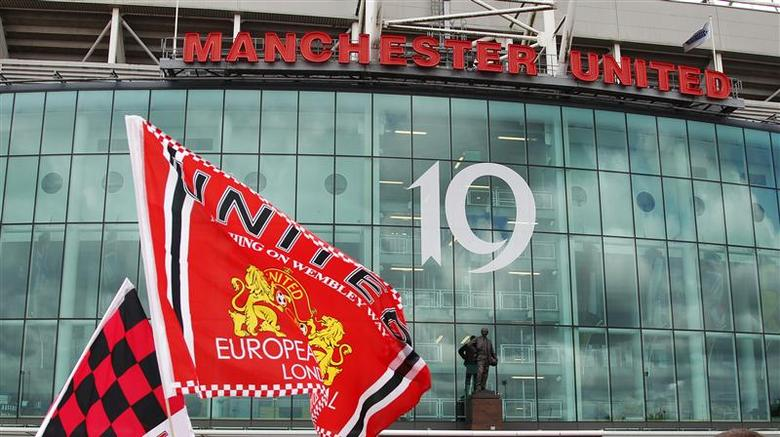 Manchester United supporters wave flags outside the stadium before their English Premier League soccer match against Blackpool at Old Trafford in Manchester, northern England, May 22, 2011. REUTERS/Darren Staples