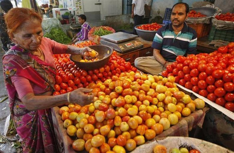 A woman buys tomatoes at a wholesale vegetable market in Ahmedabad September 11, 2013. REUTERS/Amit Dave/Files