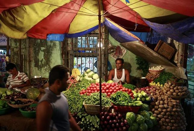 A vendor selling vegetables waits for customers at his stall at a market in Mumbai December 12, 2013. REUTERS/Danish Siddiqui/Files
