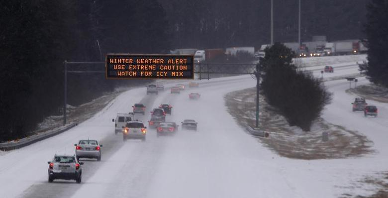 Cars drive under a traffic sign displaying winter storm warnings after a rare snowstorm in Kennesaw, Georgia, January 28, 2014. REUTERS/Tami Chappell