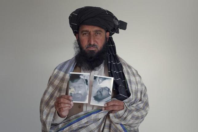 Pakistani tribesman Kareem Khan, 43, poses with images of his deceased brother Asif Iqbal (L) and son Zaenullah during an interview in Islamabad November 30, 2010. REUTERS/Mian Khursheed