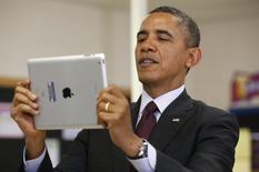 Президент США Барак Обама держит iPad во время визита в школу в Адельфи, Мэрилэнд 4 февраля 2014 года. Еврокомиссия в среду потребовала ослабить влияние США на организацию интернета, но не стала требовать усиления правительственного контроля за всемирной паутиной, чего добиваются Китай и Россия. REUTERS/Kevin Lamarque