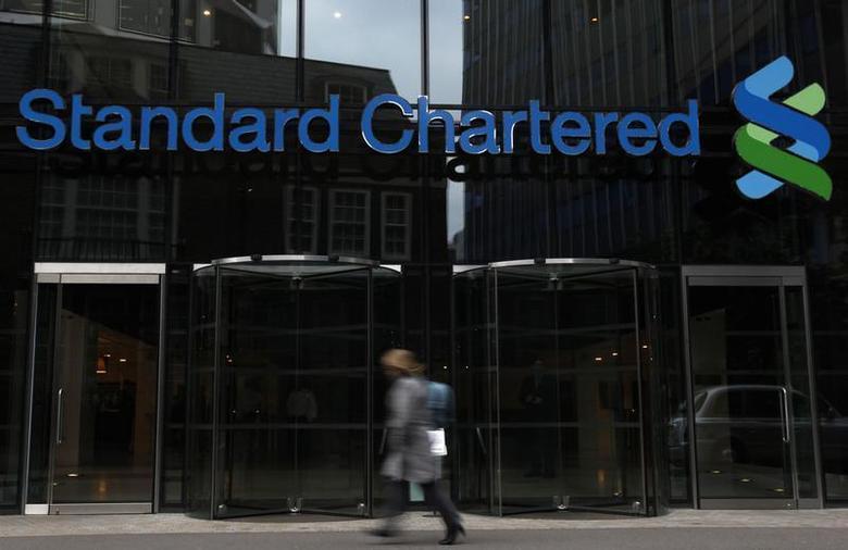 A woman walks past a Standard Chartered bank in London October 13, 2010. REUTERS/Stefan Wermuth
