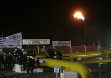 Trabalhadores participam da inauguração de um recém-concluído gasoduto, em Yacuiba. A Bolívia acrescentará 2,24 milhões de metros cúbicos de gás natural por dia ao fornecimento ao Brasil para abastecer uma central termoelétrica em Cuiabá, no momento em que o País passa por uma estiagem que eleva a demanda por geração de energia. 30/06/2011 REUTERS/Gaston Brito