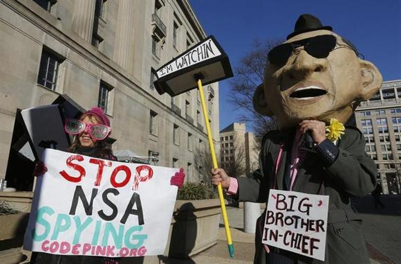 The founder of the protest group Code Pink Medea Benjamin (L) and a protester in a mask depicting U.S. President Barack Obama character as she protests against Obama and NSA before his arrival at the Department of Justice in Washington, January 17, 2014. REUTERS/Larry Downing/Files