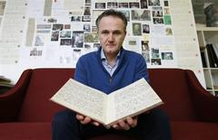 British journalist and writer Rob McGibbon poses with the diary of Olive Higgins from 1914 in his office in west London February 12, 2014. REUTERS/Suzanne Plunkett