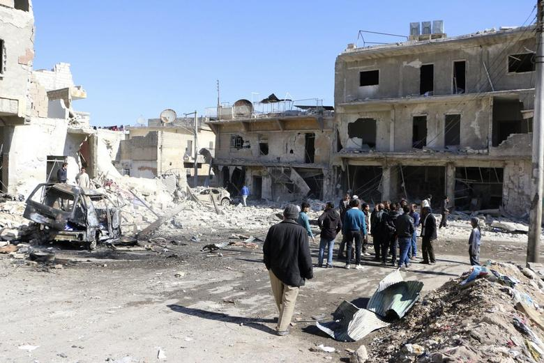 People gather at a site hit by what activists said was a barrel bomb dropped by forces loyal to Syria's President Bashar al-Assad in Haydariye district in Aleppo February 12, 2014. REUTERS/Hosam Katan
