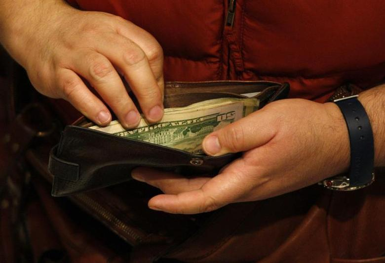 A customer opens his wallet at a Macy's cash register on Black Friday in New York in this November 26, 2010 file photo. REUTERS/Jessica Rinaldi