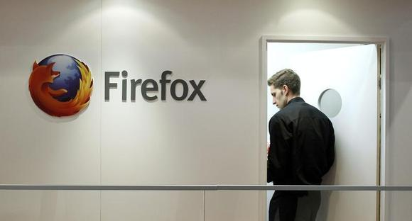 A man is seen next to a Firefox logo at a Mozilla stand during the Mobile World Congress in Barcelona, February 28, 2013. REUTERS/Albert Gea/Files