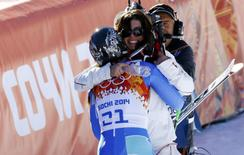 Slovenia's Tina Maze (front) hugs Switzerland's Dominique Gisin after they jointly won the women's alpine skiing downhill race at the 2014 Sochi Winter Olympics February 12, 2014. REUTERS/Kai Pfaffenbach