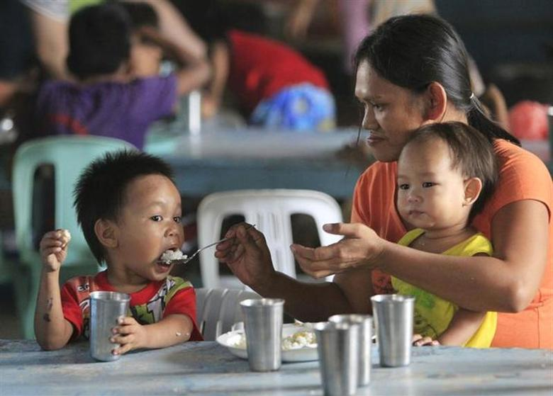 A mother divides a free meal between her children during a feeding program at a slum area in Baseco, Tondo, metro Manila January 20, 2014. REUTERS/Romeo Ranoco