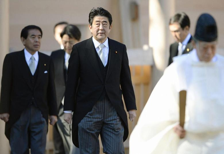 Japan's Prime Minister Shinzo Abe (C) is led by a shinto priest (R) as he pays a customary New Year's visit at Ise shrine in Ise, central Japan, in this photo taken by Kyodo January 6, 2014.REUTERS/Kyodo