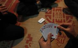 Men play cards during a ceremony in Hanoi February 10, 2014. REUTERS/Kham