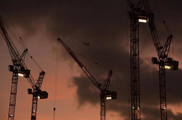 A plane flies behind cranes standing on construction sites, at dusk in London December 9, 2013. REUTERS/Toby Melville