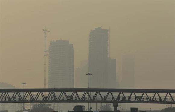 People walk on an overhead pedestrian bridge on a heavy hazy day in Beijing November 8, 2013. REUTERS/Jason Lee/Files