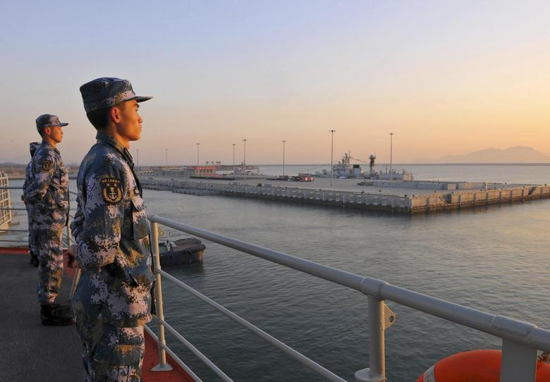 Chinese naval soldiers stand guard on China's first aircraft carrier Liaoning, as it travels towards a military base in Sanya, Hainan province, in this undated picture made available on November 30, 2013. Ongoing tensions with the Philippines, Japan and other neighbours over disputed territories in East and South China Sea were heightened by China establishing a new airspace defense zone. REUTERS/Stringer