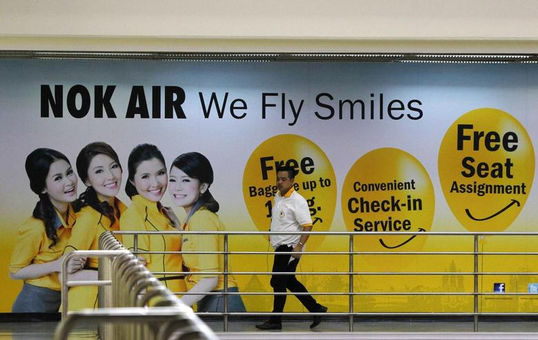 A Nok Air staff member walks past a commercial for the airlines at Don Muang International Airport in Bangkok June 20, 2013. REUTERS/Chaiwat Subprasom