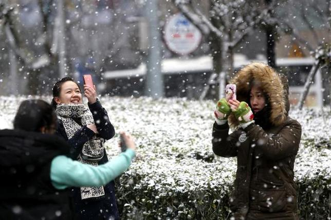 Women use their mobile phones to take pictures of the snow at Lujiazui financial district of Pudong, in Shanghai February 10, 2014. REUTERS/Aly Song