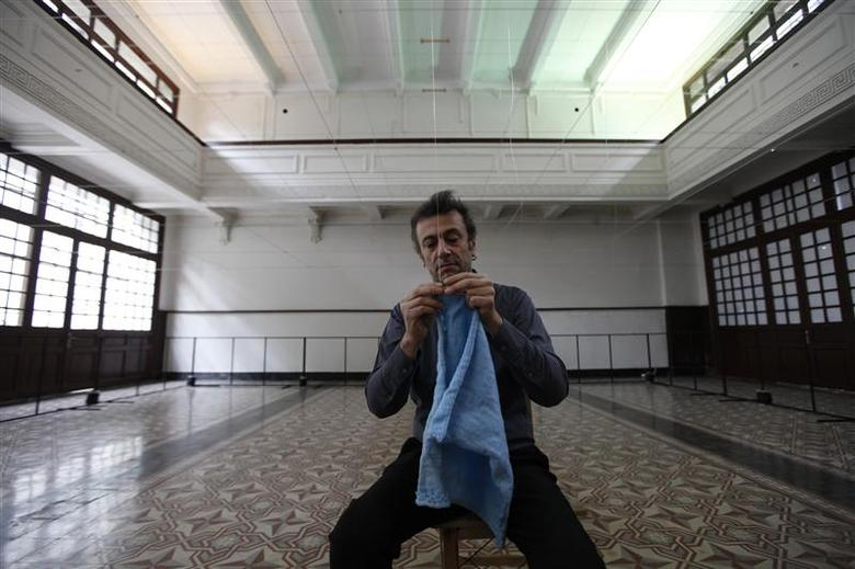 Artist Kutlug Ataman attaches the first cloth to start his art project ''Silsel'' at Galata Greek Primary School in Istanbul in this May 12, 2012 file photo. REUTERS/Murad Sezer