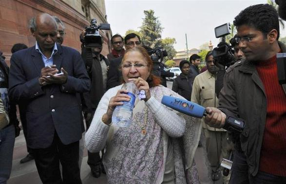 Sumitra Mahajan, a parliamentarian and a leader of Bharatiya Janata Party (BJP), drinks water after she rushed out of the parliament in New Delhi February 13, 2014. REUTERS/Adnan Abidi