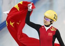 """Китаянка Цзяжоу Ли празднует победу на льду арены """"Айсберг"""" в Сочи 13 февраля 2014 года. Китайская конькобежка Цзяжоу Ли стала в четверг самой быстрой в финале дистанции на 500 метров в шорт-треке, выиграв первую золотую медаль для Китая на зимней Олимпиаде в Сочи. REUTERS/Lucy Nicholson"""