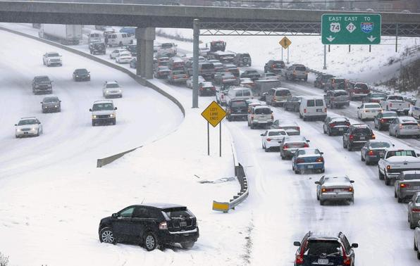 Slow moving motorists are seen on a freeway leaving downtown Charlotte as snow continues to fall in Charlotte, North Carolina February 12, 2014. REUTERS/Chris Keane