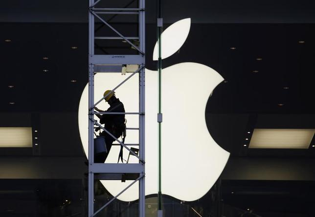 A worker climbs outside an Apple store in Hong Kong April 10, 2013. REUTERS/Bobby Yip/Files