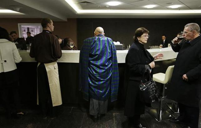 Afghan President Hamid Karzai (C) waits to order a coffee in the presidential lounge before the opening ceremony of the 2014 Winter Olympics in Sochi, February 7, 2014. REUTERS/David Goldman/Pool