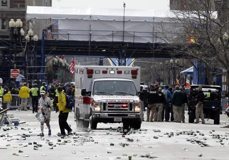 A runner is escorted from the scene after explosions went off at the 117th Boston Marathon in Boston, Massachusetts April 15, 2013. REUTERS/Jessica Rinaldi