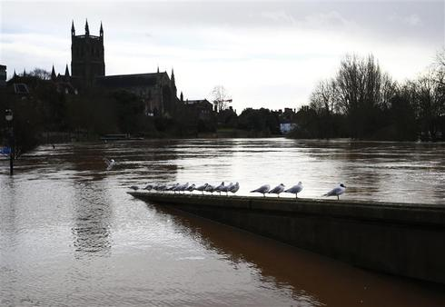One dead as storms batter flooded Britain