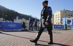 A Cossack in traditional attire walks in downtown Rosa Khutor during the Sochi 2014 Winter Olympic Games, February 13, 2014. REUTERS/Michael Dalder