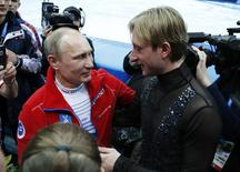 Russian President Vladimir Putin (L) greets Yevgeny Plushenko, a member of the gold medal-winning Russian figure skating team, during the 2014 Sochi Winter Olympics, February 9, 2014. REUTERS/Lucy Nicholson